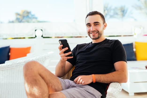 ハンサムな観光客は、歩道のカフェでリラックスしながら携帯電話でsmsを読んだりテキストメッセージを送ったりします。
