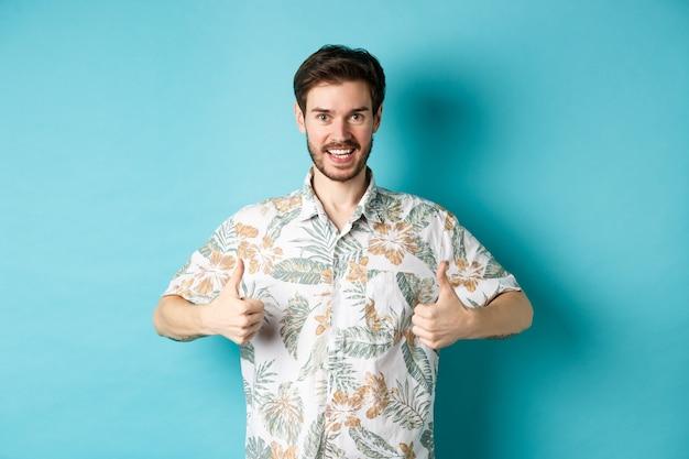 Красивый турист показывает палец вверх и говорит да, хвалит хорошее туристическое агентство, одетый в гавайскую рубашку, стоит на синем фоне.