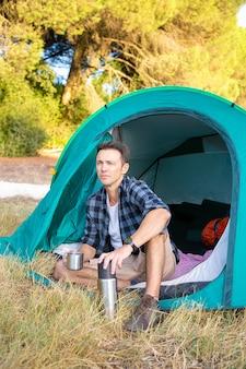 テントに座って景色を見ているハンサムな観光客。自然にキャンプし、魔法瓶からお茶を飲む思いやりのある白人旅行者。観光、冒険、夏休みのコンセプトをバックパッキング
