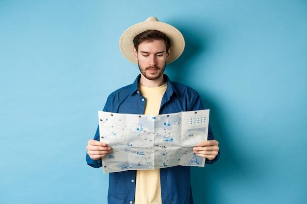 Красивый турист с летней шляпой, читая карту, ищет достопримечательности в отпуске, стоя на синем фоне.