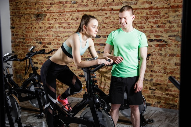 Handsome trainer and beautiful woman exercising on bicycle