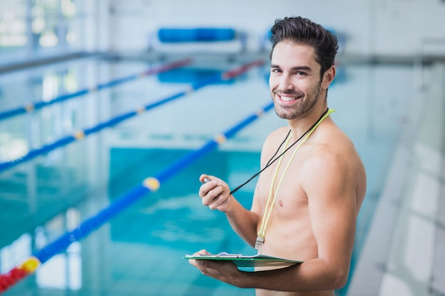 Handsome trainer holding stopwatch and clipboard at the pool