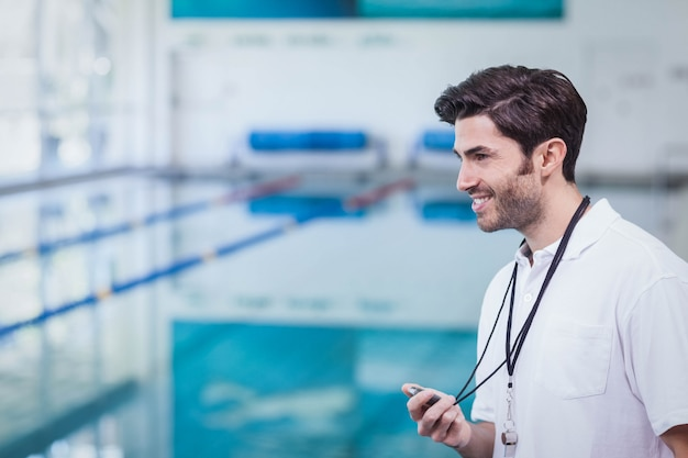 Handsome trainer holding stopwatch at the pool
