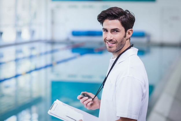 Handsome trainer holding stopwatch and reading clipboard at the pool