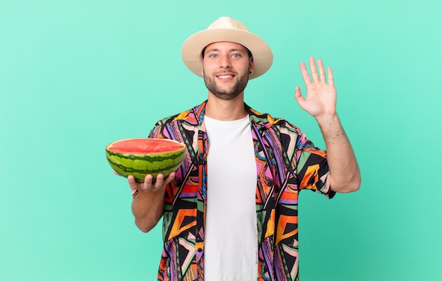 Handsome traveler man smiling happily, waving hand, welcoming and greeting you and holding a watermelon. holidays concept