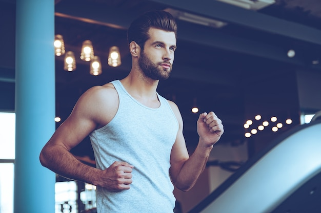 Handsome on treadmill. low angle view of young handsome man in sportswear running on treadmill and looking away at gym