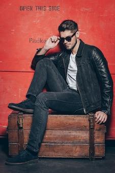 ハンサムな宝物。赤い背景に対して木製の胸に座っている間彼のサングラスを調整するハンサムな若い男