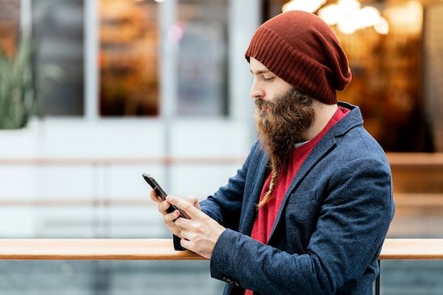 실내 유리 울타리에 기대어 스마트 폰을 사용하여 모자와 파란색 재킷에 잘 생긴 유행 힙 스터