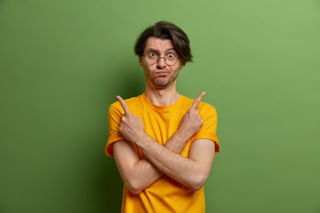 Handsome unaware adult man hesitates between two good choices, points sideways, crosses hands over chest, indicates left and right, cannot choose what to pick, dressed in vivid yellow t shirt