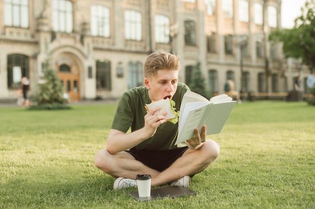 食欲をそそるサンドイッチを食べるハンサムな大学生