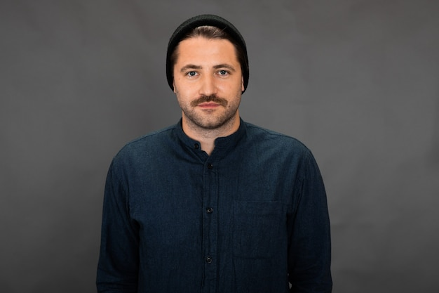 Handsome unshaven guy in knitted cap posing on gray studio backdrop