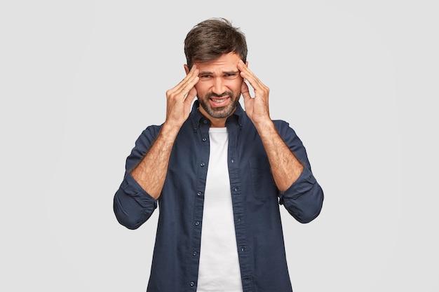 Красивый небритый мужчина держит руки на висках, недовольно хмурится, ужасно болит голова, одет в бело-синюю рубашку, позирует у белой стены. озадаченный недовольный мужчина позирует в помещении