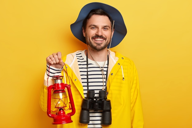 Handsome unshaven man carries kerosene lamp, binoculars, ready for expedition or journey, wears hat and raincoat, isolated over yellow wall
