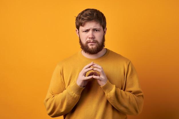 ハンサムな無精ひげを生やした男はトリッキーな邪悪な計画を持っており、指を尖らせ、カメラを不思議に見て、良いアイデアを考え、カジュアルなセーターと眼鏡をかけ、バラ色の背景の上にポーズをとり、スペースをコピーします