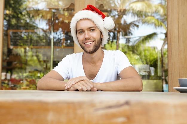 Uomo con la barba lunga bello in cappello di babbo natale con pelliccia che guarda l'obbiettivo e sorridente felicemente, che celebra il nuovo anno mentre è in vacanza nel paese tropicale