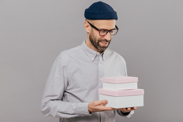 Handsome unshaven man with brislte holds two boxes, happy to recieve present from friend on birthday