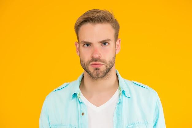 강모가 있는 면도하지 않은 잘생긴 남자. 남성 여름 캐주얼 패션 스타일. 진지한 남자는 노란색 배경에 머리를 손질했다. 인간의 감정. 트렌디한 헤어스타일을 한 섹시한 소년은 셔츠를 입는다.