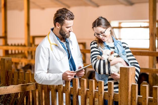 Красивый ветеринар в медицинском халате и молодая женщина заботятся о козленке, стоящем в помещении в сарае