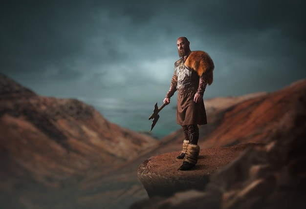 Handsome viking with axe dressed in traditional nordic clothes standing on the top of rocky mountain. scandinavian ancient warrior