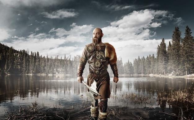 Красивый викинг с топорами в руках, одетый в традиционную скандинавскую одежду, стоит у озера. древний воин у реки, северный лес