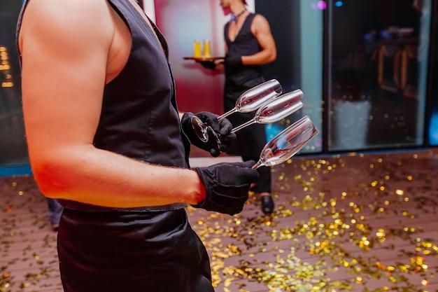 클럽에서 샴페인 나이트 파티를 위해 벌거 벗은 손에 빈 안경을 들고 잘 생긴 웨이터