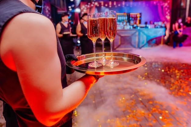 샴페인으로 가득 찬 안경을 벗은 손 쟁반에 들고 있는 잘생긴 웨이터 클럽에서 밤 파티