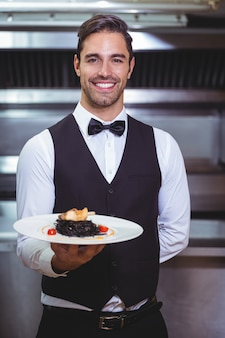 Handsome waiter holding a plate of squid ink spaghetti