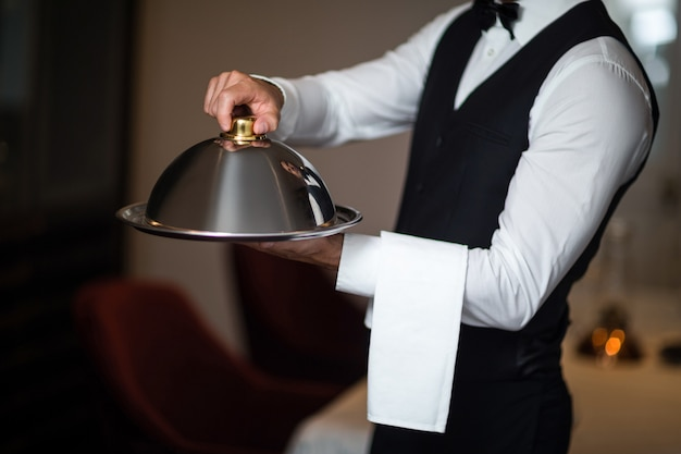 Handsome waiter holding tray