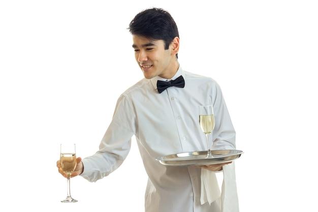 흰 셔츠에 나비와 잘 생긴 웨이터가 흰 벽에 고립 된 와인 잔을 뻗어