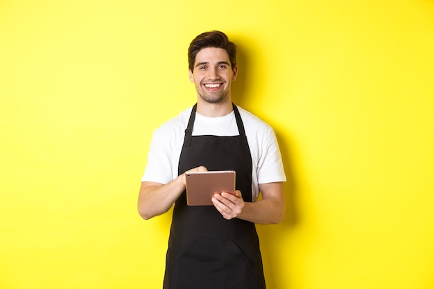 Handsome waiter taking orders, holding digital tablet and smiling, wearing black apron uniform, standing over yellow background.