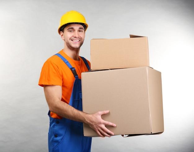 가벼운 표면에 골 판지 상자와 잘 생긴 창고 노동자