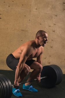 Handsome weightlifter preparing for training with barbell