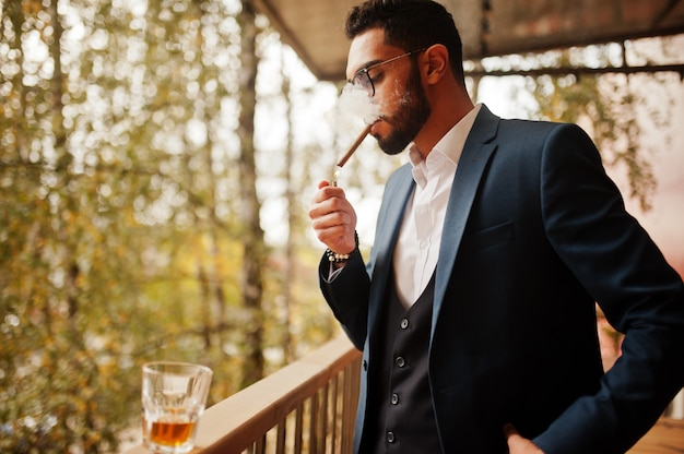 Handsome well-dressed arabian man smoke cigar at balcony of pub.