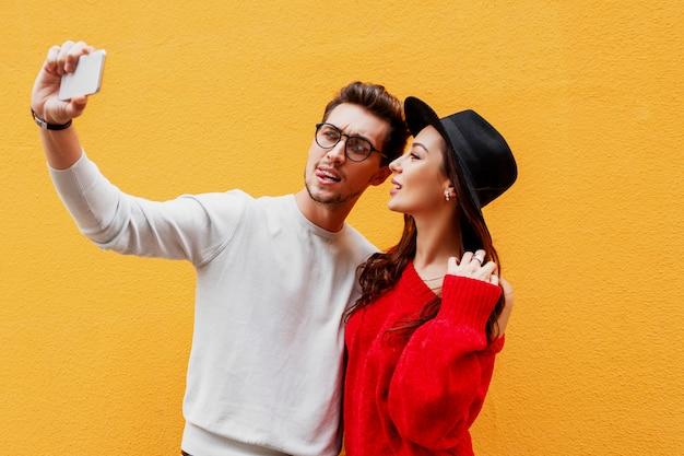 ひげとセルフポートレートを作るかわいい遊び心のあるブルネットの女性とハンサムな白人男性と手で兆候を示しています。前向きな気分。黄色の壁。モバイルデバイスを使用してカップル。
