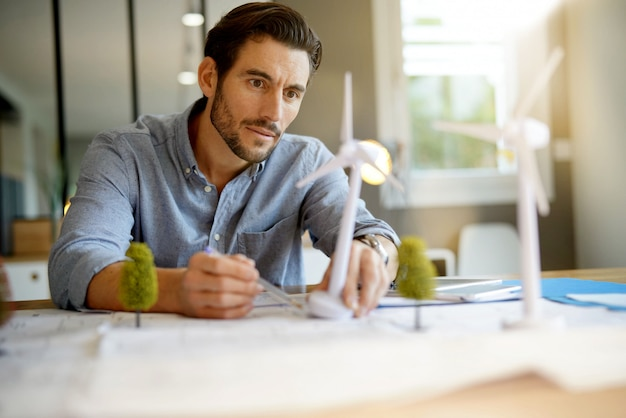 Handsome wind turbine engineer working in modern office