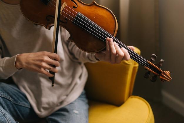 Красивая женщина-музыкант играет на скрипке в своем доме, сидя на мягком стуле, крупным планом