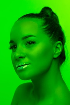 Handsome woman's portrait isolated on green studio background in neon light, monochrome. beautiful female model. concept of human emotions, facial expression, sales, ad, fashion and beauty.