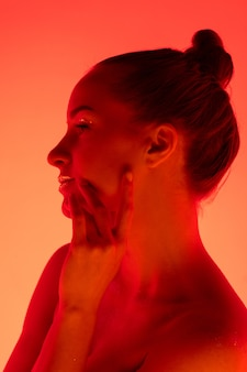 ネオンの光、モノクロで赤オレンジ色のスタジオの背景に分離されたハンサムな女性の肖像画。美しい女性モデル。人間の感情、顔の表情、販売、広告、ファッション、美容の概念。