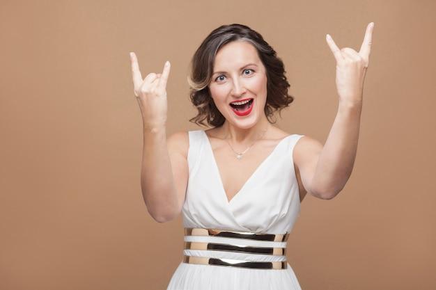 ロックンロールのサインと叫びを示すハンサムな女性。白いドレス、赤い唇、暗い巻き毛の髪型で感情的に表現する女性。スタジオショット、屋内、ベージュまたは薄茶色の背景に分離