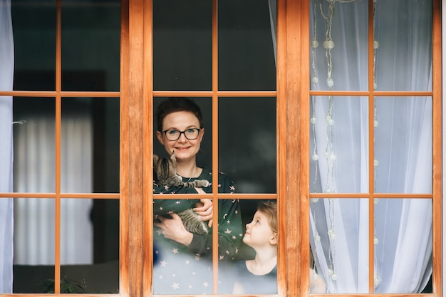 Handsome woman with kitten in hands  looks through big window with her little beautiful daughter