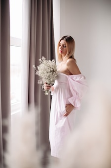 白い花の彼女のボケを見て中程度のブロンドの髪を持つハンサムな女性