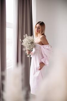 Bella donna con capelli biondi medi che guarda il suo mazzo di fiori bianchi