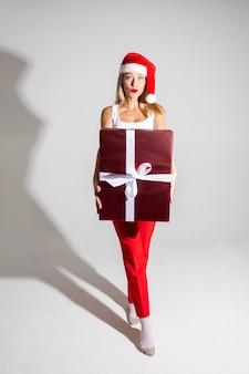 赤と白のクリスマスの帽子を持つハンサムな女性は大きなプレゼントを保持します