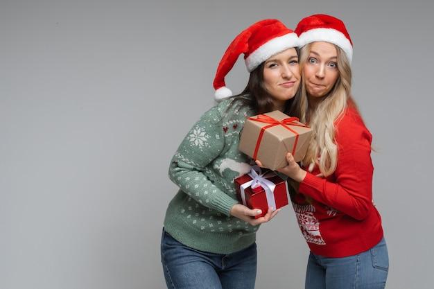 빨간색과 흰색 크리스마스 모자를 쓴 잘생긴 여자 친구들은 서로 선물을 들고 미소를 짓습니다