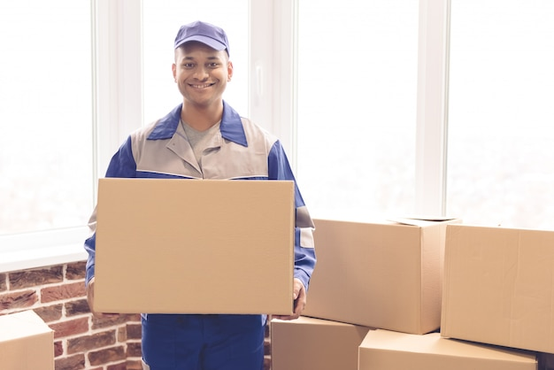 Handsome worker in blue uniform is holding a box.