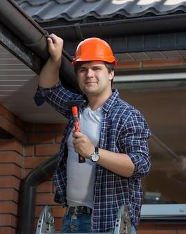 ステップのはしごにハンマーでポーズをとるヘルメットのハンサムな労働者