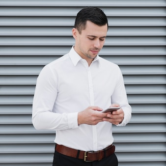 Handsome working man checking phone