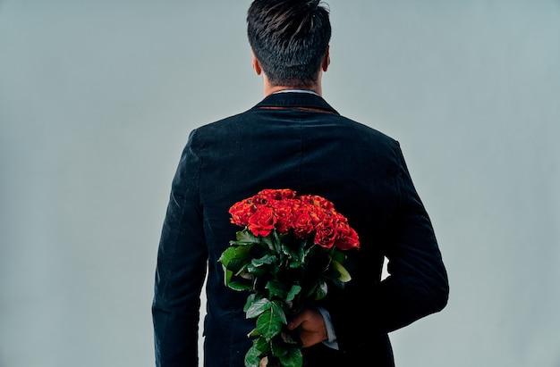 정장을 입은 잘생긴 젊은이가 회색 배경에 빨간 장미를 들고 서 있습니다. 발렌타인 데이. 결혼 제안. 기념일.