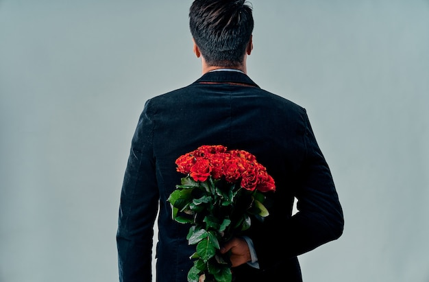 Handsome yound man in suit is standing with red roses behind the back on grey background. st. valentine's day. marriage proposal. anniversary.