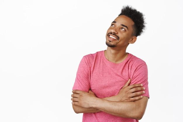 Красивый молодой афро-американский мальчик 20-х годов, парень со скрещенными руками, задумчиво смотрит в левый верхний угол, улыбается, думая, воображая что-л., стоя на белом